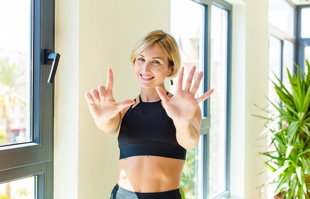 Pretty blonde woman smiling and looking friendly, showing number seven or seventh with hand forward, counting down