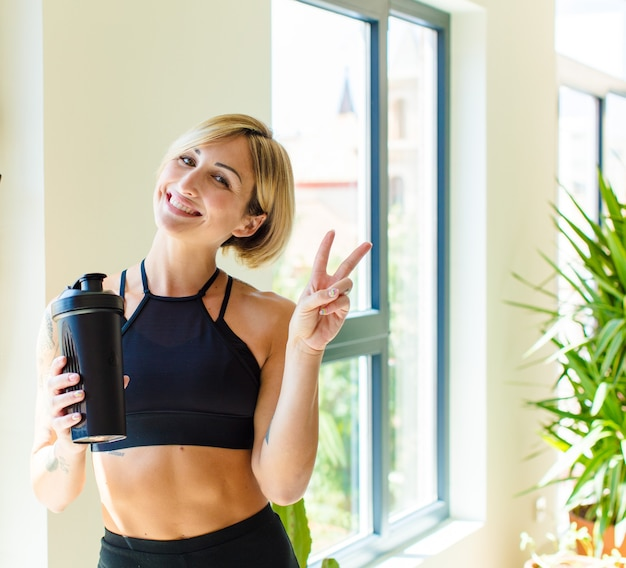 Pretty blonde woman smiling and looking happy, friendly and satisfied, gesturing victory or peace with both hands