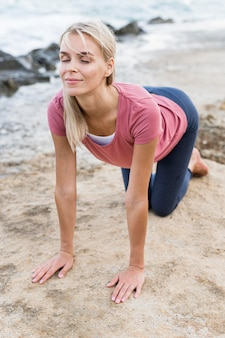 Pretty blonde woman stretching at the beach