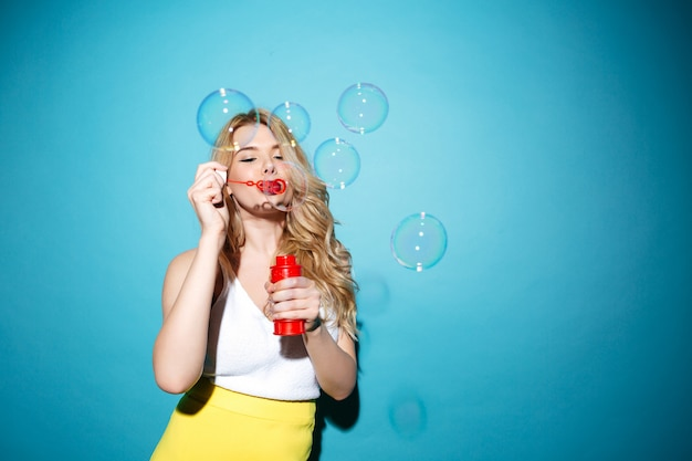 Pretty blonde woman in summer clothes blowing soap bubbles