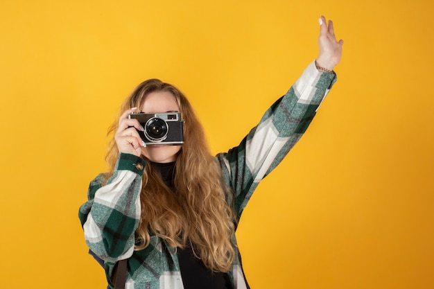 かなり金髪の女性が古いカメラで写真を撮る黄色