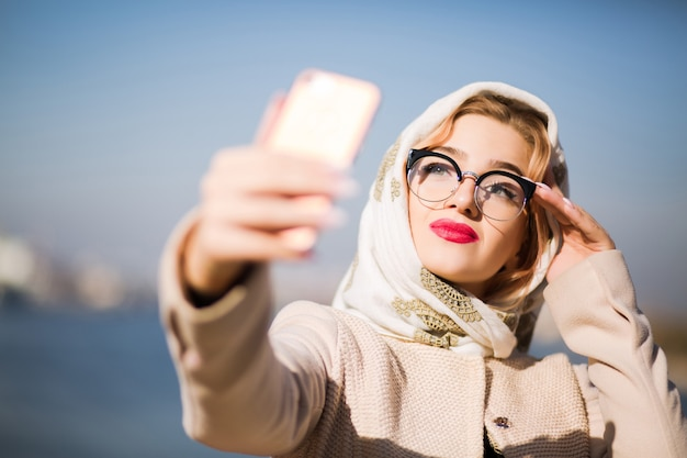 携帯電話で自分撮りをしているかなり金髪の女性。女性はショールと眼鏡をかけています