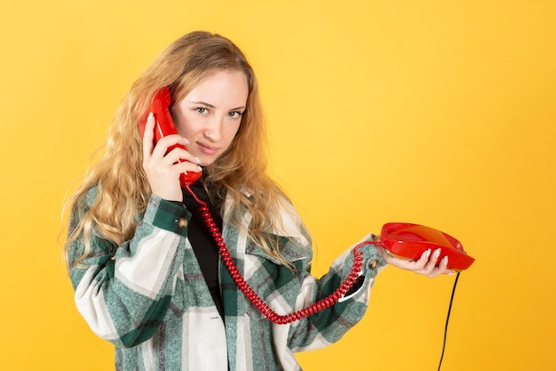 黄色の背景で、電話で話しているかなり金髪の女性