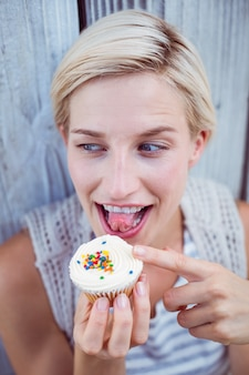 Pretty blonde woman tasting the cupcake