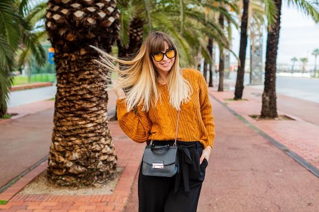 예쁜 금발의 여인이 바르셀로나를 여행하며 가을을 즐기고 있습니다.