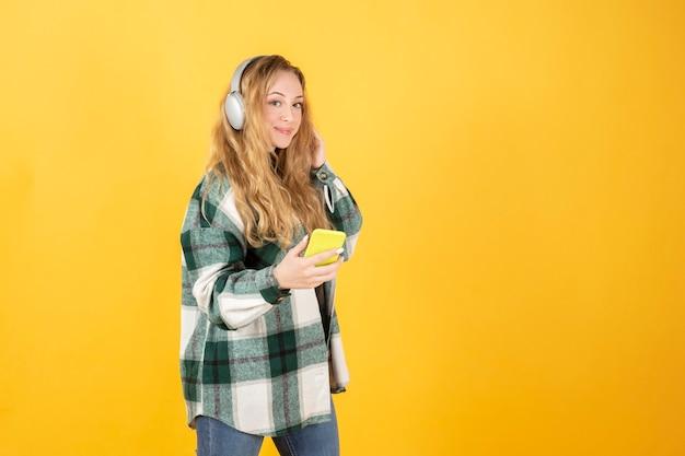 携帯電話とヘッドフォンを使用してかなり金髪の女性