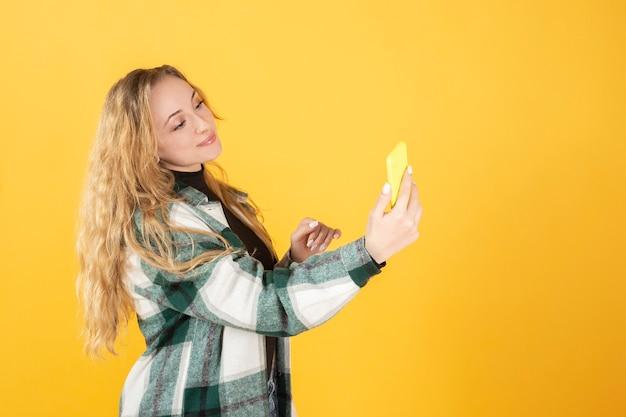 携帯電話の黄色のトーンを使用してかなり金髪の女性