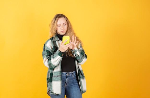 スマートフォンを使用してかなり金髪の女性幸せな笑顔の黄色の背景