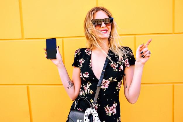 花のドレスを着て、黄色の壁に近いポーズとスマートフォンを保持しているかなりブロンドの女性