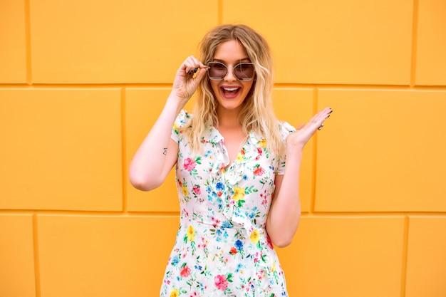 Довольно блондинка женщина в цветочном платье, позирует возле желтой стены