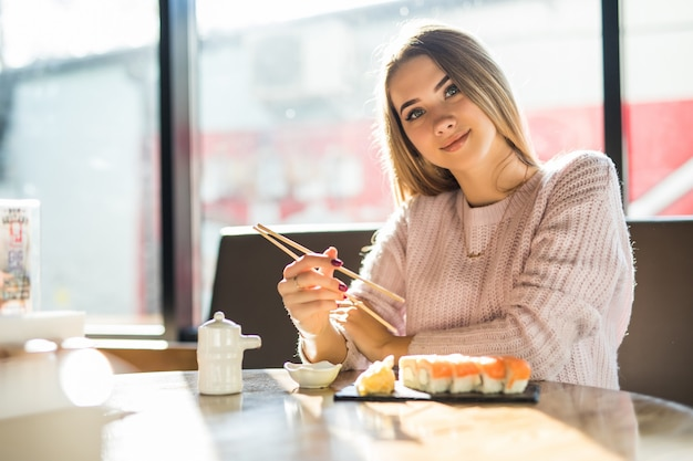 Pretty blonde woman in white sweater eating sushi for lunch at a small caffe