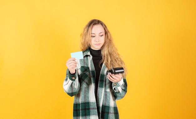 黄色の背景に、データフォンとクレジットカードを持つかなり金髪の女性
