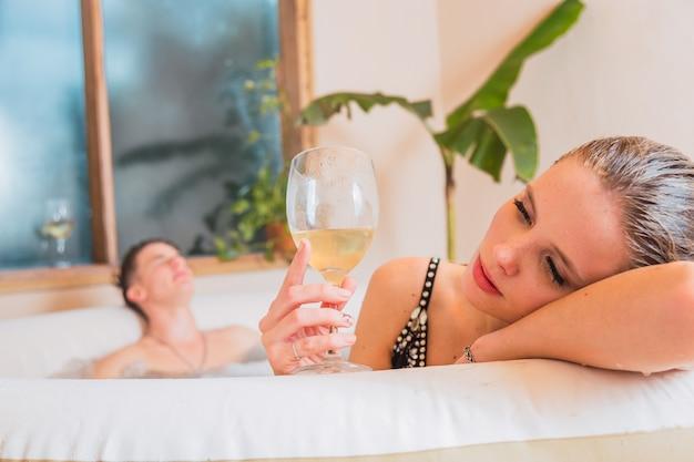 グラスワインを片手に金髪の美女が、彼氏がお風呂の向こう側でがっかりしていると思う。緑の植物と白い部屋。