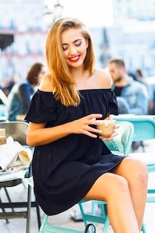 Довольно блондинка с ярким макияжем, ожидание в одиночестве, сидя на террасе кафетерия, в красивом центре города, в солнечный день, стильный повседневный наряд