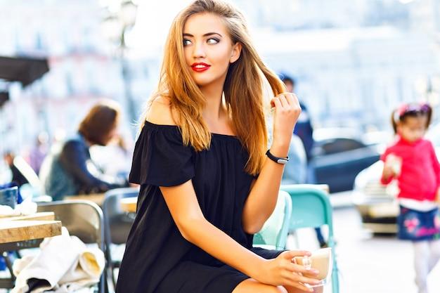 明るいメイクとかなりブロンドの女性、一人で待って、カフェテリアテラスに座って、美しい市内中心部、晴れた日、スタイリッシュなカジュアルな服装で