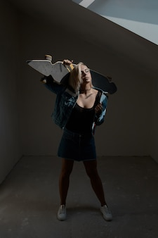 Pretty blonde woman with longboard in dark room