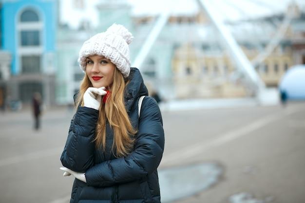 ニット帽をかぶって、街歩きを楽しんでいる赤い口紅のきれいなブロンドの女性。テキスト用のスペース