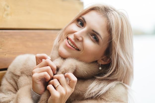 木製の壁に30歳の毛皮のコートできれいな青い目のブロンドの女性..贅沢なライフスタイルのショッピング