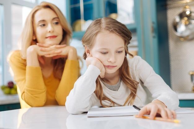 Довольно скучающая белокурая девушка сидит за столом со своим блокнотом, а ее мать сидит за ее спиной и улыбается