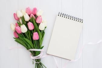 空のノートブックとチューリップの花のかなりの花束