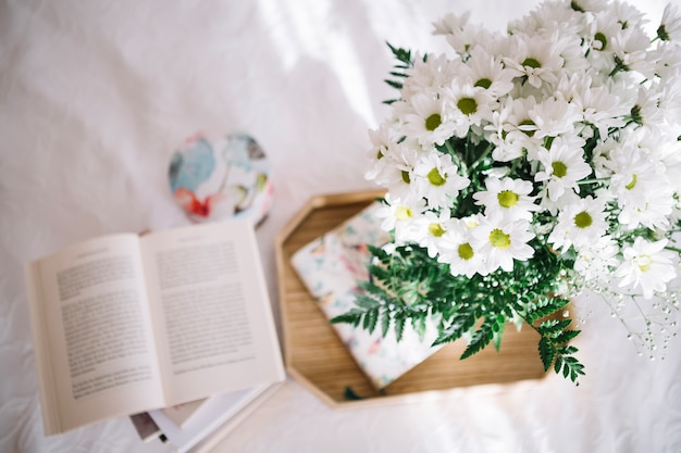 Pretty bouquet on tray near opened book