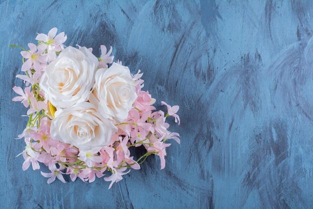 Grazioso bouquet di fiori bianchi e rosa sul blu.
