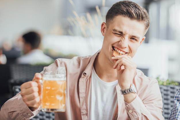 Симпатичный мальчик кусает печенье и пьет пиво в кафе.