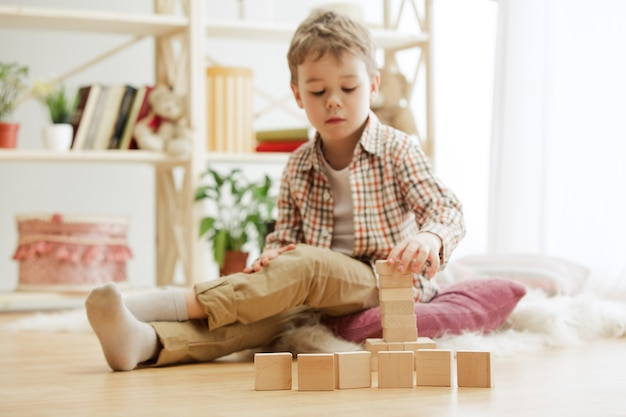 Bel ragazzo che gioca con i cubi di legno a casa