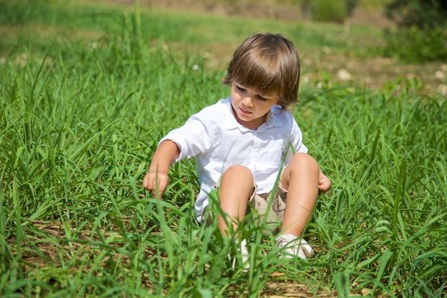 Pretty boy sitting on grass