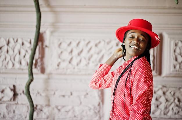 かなり三つ編みビジネスアフリカ系アメリカ人女性明るい偉そうな人フレンドリーなウェアオフィスの赤いシャツと帽子。