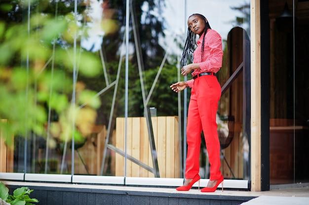 かなり三つ編みビジネスアフリカ系アメリカ人女性明るい偉そうな人フレンドリーなウェアオフィスの赤いシャツとズボン。