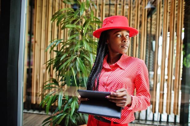 かなり三つ編みビジネスアフリカ系アメリカ人女性明るい偉そうな人フレンドリーなウェアオフィス赤いシャツ、帽子、ズボン、手にタブレットを保持します。