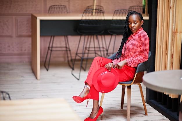かなり三つ編みビジネスアフリカ系アメリカ人女性明るい偉そうな人フレンドリーなウェアオフィス赤いシャツ、帽子、ズボン、椅子に座っています。