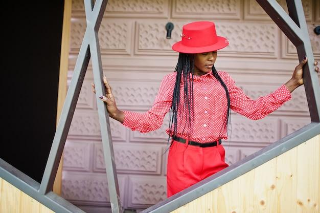 かなり三つ編みビジネスアフリカ系アメリカ人の女性明るい偉そうな人フレンドリーなウェアオフィスの赤いシャツ、帽子、ズボン。