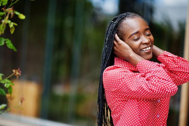 かなり三つ編みビジネスアフリカ系アメリカ人女性明るい偉そうな人フレンドリーウェアオフィス赤いシャツ。