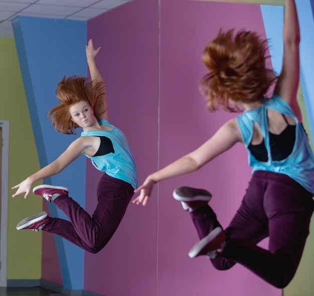 Pretty break dancer jumping up and looking in mirror