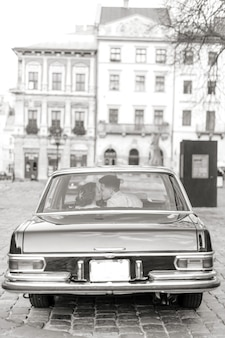 Pretty bride and handsome groom kissing and hugging in the retro car. wedding day, retro style, old city center.