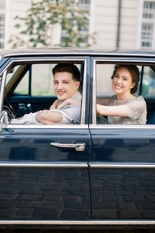 Pretty bride and handsome groom in the retro car in old city center