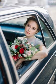 Pretty bride in luxury wedding dress sitting inside of retro car and holding wedding bouquet