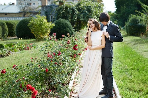 緑の公園の背景、結婚式の写真、美しいカップル、結婚式の日、肖像画に立っている長い巻き毛と花婿を持つかわいい花嫁。