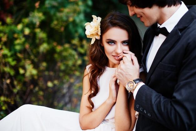 긴 곱슬 머리와 녹색 잎 배경, 웨딩 사진, 아름 다운 커플에서 서로 가까이 서있는 신랑 예쁜 신부.