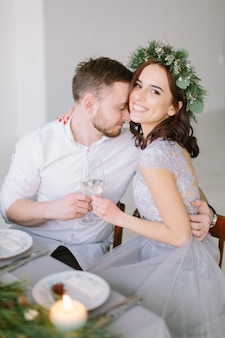 Pretty bridesmaid in pine wreath and groomman at the wedding table hugging and kissing