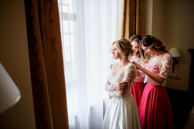 Довольно подружки невесты в розовых платьях помогают невесте надеть свадебное платье