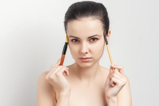 化粧スキンケア化粧品のトリミングされたビューを適用するかなりブルネット。
