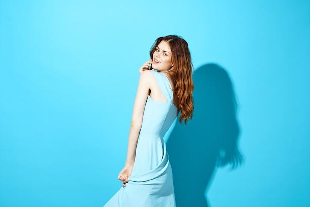 魅力的な孤立した背景をポーズするかなりブルネットの青いドレス。高品質の写真