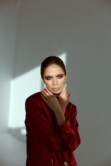 Pretty brunette bright makeup hands near face red jacket fashion glamor