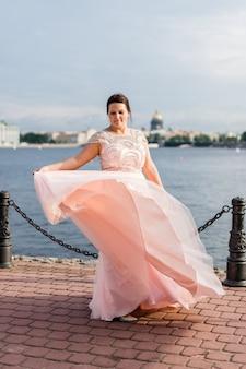 Pretty brunette caucasian model waving hem of pastel pink beaded dress on quay.