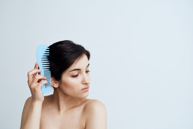 Pretty brunette combs hair bare shoulders shower grooming