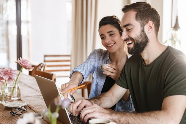 Pretty brunette couple man and woman drinking coffee and working on laptop together while sitting at table at home