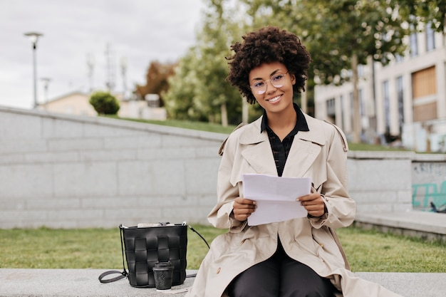 Pretty brunette curly woman in eyeglasses and beige trench coat holds paper sheet, smiles and sits outdoors